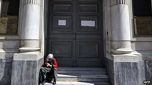 A man with a bag of coins walks past the headquarters of the Bank of Greece