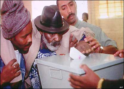 An elderly black voter casts his vote