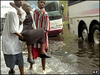 An elderly woman is carried to board an evacuation bus out of New Orleans