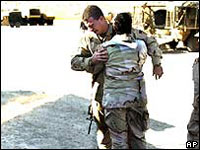 US soldier is comforted as he stands by the body of a comrade killed in Iraq