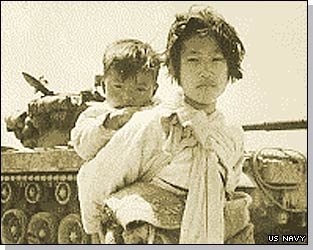 A Korean girl with her brother on her back in front of an M-26 tank in Haengju, Korea