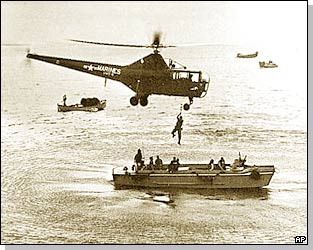 A hovering US Marine helicopter picks up personnel from a landing barge in Inchon harbour