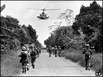 US Army helicopter provides cover for Vietnamese Marines as they advance into the town of Binh Ngia, 30 Dec 1964