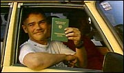 An East German holds up his new West German passport as he crosses border