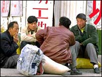 Migrant workers sit on the street, chatting