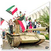 Kuwaitis celebrate on a tank after the allied forces reclaimed Kuwait City
