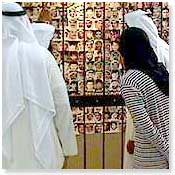 Kuwaitis look at a wall of photographs of the missing