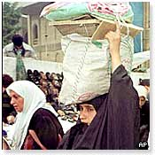 An Iraqi woman carrying her monthly food ration