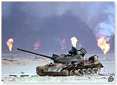 A burnt-out tank in front of burning oil wells in Kuwait