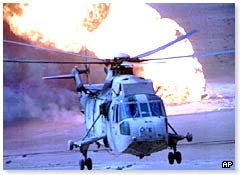 A military helicopter flies past a burning oil well in Kuwait