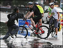 Cyclists going through water caused by burst mains