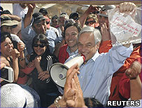 Chilean President Sebastian Pinera holds a note from the miners