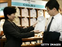 2005 photo of environment minister Yuriko Koike showing a customer a lightweight shirt at the CoolBiz section of a Tokyo department store