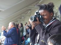 A School Reporter takes photos in a stadium