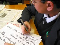 School Reporter writing on a cue card