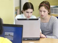 School Reporters using a laptop