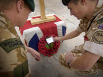Soldiers laying a wreath of poppies