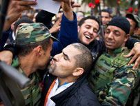 Protesters in Tunisia kissing and hugging soldier during the uprising in 2011 (AFP)