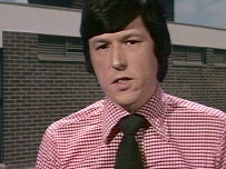 John Craven in the 1980s wears a pink shirt and black tie.