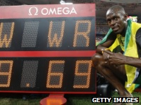Usain Bolt sits with his world record photo.