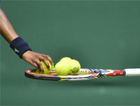 Ball girl places tennis balls on a racquet