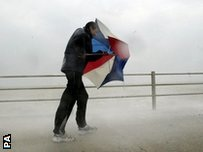 A man battling with an umbrella