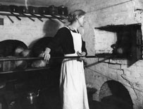 Woman putting bread into an oven