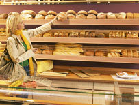 Woman reaching for loaf of bread in a shop