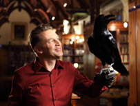 Chris Packham holds a raven
