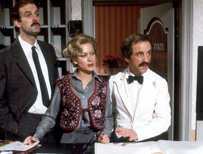 Basil, his wife and Manuel at reception desk at Fawlty Towers