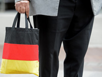Man carrying shopping bag in the colours of the German flag