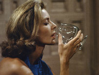 Lauren Bacall drinking out of a glass