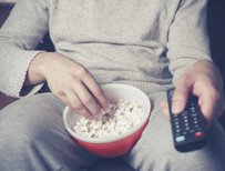 Man watching television with bowl of popcorn