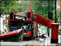 Bombed bus photgraphed from the front, showing destroyed roof and side.