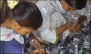Indian children making bangles