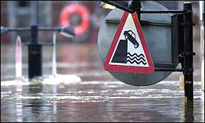 Road sign nearly engulfed by floodwater