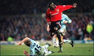 Andy Cole rides a tackle from Alan Kernaghan as United get the better of their rivals