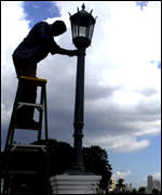 A workman fixes a streetlamp