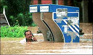 A man at a flooded phone box in Terengganu, Malaysia