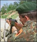 [ image: A fighter of the Kosovo Liberation Army watches a road in the province's Drenica region]