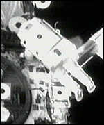 Astronauts secure the mast with bolts