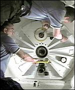 Astronauts open the hatch from the shuttle to the space station