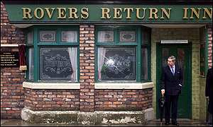 Prince Charles shelters from the rain in the doorway of the famous Rovers Return pub