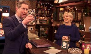 Landlady Natalie Barnes, played by actress Denise Welch, serves Prince Charles a scotch, presumably on the house