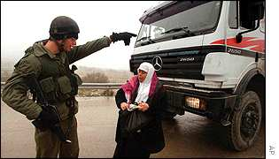 Soldier stops Palestinian woman near Jewish settlement, West Bank