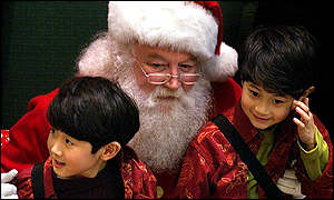 Santa Claus entertains Chinese twins in a Hong Kong shopping centre