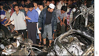 Crowds examine the wreckage outside a church in Jakarta
