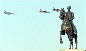Iraqi warplanes fly by a statue of Iraqi President Saddam Hussein