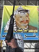 Palestinian militant in front of banner of Yasser Arafat