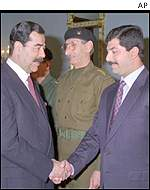 Saddam Hussein shakes hands with his younger son Qusay (right)
